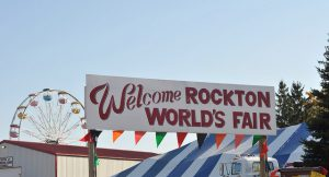 Sign welcoming visitors to the Rockton World's Fair. Ferris Wheel, barns, and marquees in background
